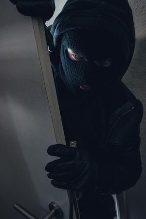 dangerous burglar sneaking into a victim's home Stok Fotoğraf