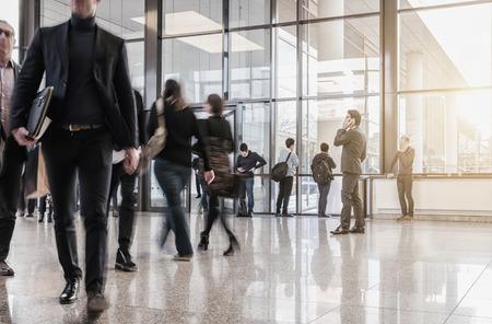 Gens d'affaires marchant dans le couloir de la foire commerciale Banque d'images