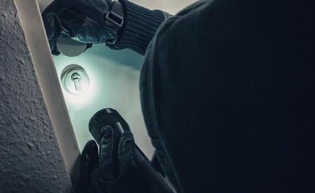 burglar with torch entering into a house door Stok Fotoğraf