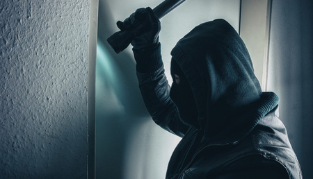 burglar with torch breaking and entering into a victim's home Stok Fotoğraf