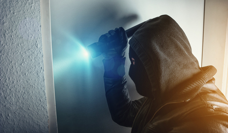 burglar with torch breaking and entering house door at night Stok Fotoğraf
