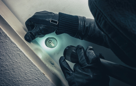 burglar with flashlight breaking and entering into a victim's home