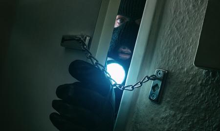 burglar with flashlight breaking into a victim's home at night Stok Fotoğraf