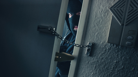 burglar with crowbar breaking into a victim's home door with chain