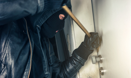 burglar with crowbar breaking and entering a house door at night Stok Fotoğraf