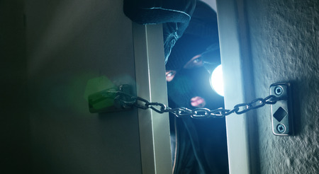 dangerous burglar sneaking into the house with a torch in his hand Stok Fotoğraf