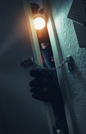 burglar with torch entering a door with chain at night Stok Fotoğraf