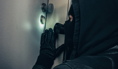 Masked burglar with flashlight breaking into a house door at night