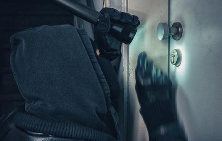 Burglar with lock picking tools breaking into a house door
