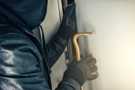 burglar with crowbar breaking and entering a victim's house door at night