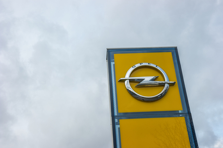 ag: AACHEN, GERMANY FEBRUARY, 2017: Opel official dealership logo over cloudy sky. Opel AG is a German automobile manufacturer and a subsidiary of the American General Motors Company.