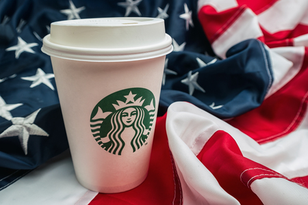 AACHEN, GERMANY FEBRUARY, 2017: Starbucks takeaway coffee cup on a america flag. Starbucks is the large largest coffeehouse company in the world.