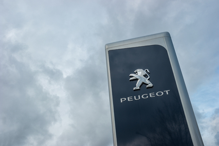 psa: AACHEN, GERMANY FEBRUARY, 2017: Peugeot dealership sign against cloudy sky. Peugeot is a French automobile manufacturer and part of Groupe PSA.