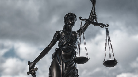 Statue of Justice symbol with dark clouds Stock Photo