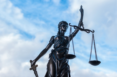 Statue of Justice symbol with cloudy sky background