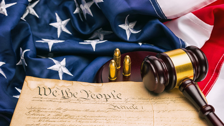 Costituzione americana con giudice martelletto e cartucce di pistola su una bandiera america Archivio Fotografico