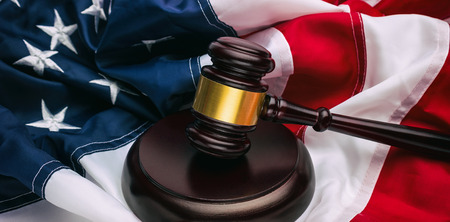 Wooden gavel and US flag Stock Photo
