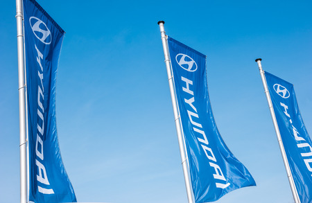 AACHEN, GERMANY MARCH, 2017: Hyundai flags against blue sky. Hyundai Motor Company is a South Korean multinational automotive manufacturer founded at 1967th