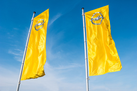 AACHEN, GERMANY MARCH, 2017: Opel flags against blue sky at the Opel Store. Opel AG is a German automobile manufacturer.