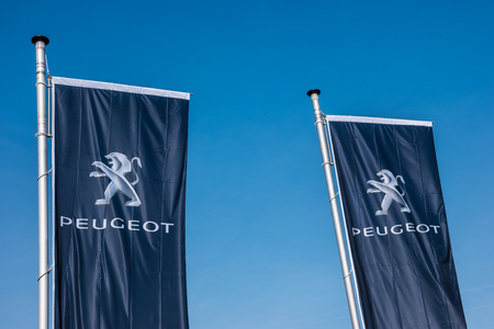 psa: AACHEN, GERMANY MARCH, 2017: Peugeot flags against blue sky at the Peugeot store. Peugeot is a French brand cars, part of PSA Peugeot Citroen.