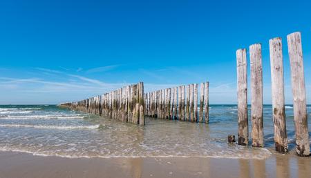 break chain: Wooden Groyne on the Beach in the Netherlands Stock Photo