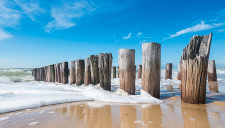 Breakwaters in waves on the beach at the north sea in Domburg Holland