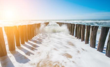 Twee parallelle rijen verweerde houten golven op het strand
