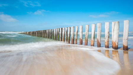 stakes: Wave breaker made of wooden stakes on the beach Stock Photo