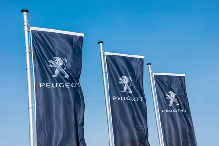 AACHEN, GERMANY MARCH, 2017: Peugeot flags against blue sky at the Peugeot store. Peugeot is a French brand cars, part of PSA Peugeot Citroen.