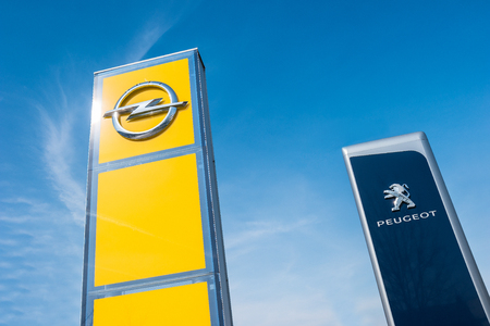psa: AACHEN, GERMANY MARCH, 2017: Peugeot and Opel dealership sign against blue sky. Peugeot is a French automobile manufacturer and part of Groupe PSA. Opel AG is a German automobile manufacturer. Editorial