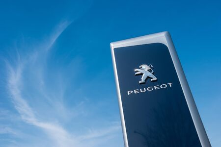psa: AACHEN, GERMANY MARCH, 2017: Peugeot dealership sign against blue sky. Peugeot is a French automobile manufacturer and part of Groupe PSA. Editorial