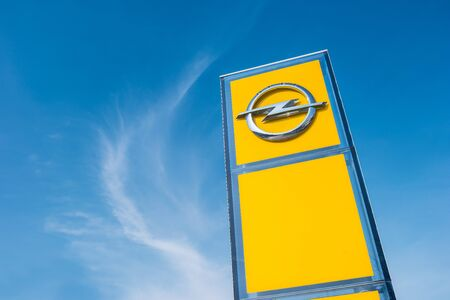 ag: AACHEN, GERMANY MARCH, 2017: Opel official dealership logo over cloudy sky. Opel AG is a German automobile manufacturer. Editorial