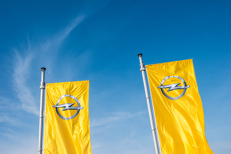 ag: AACHEN, GERMANY MARCH, 2017: Opel flags against blue sky at the Opel Store. Opel AG is a German automobile manufacturer.