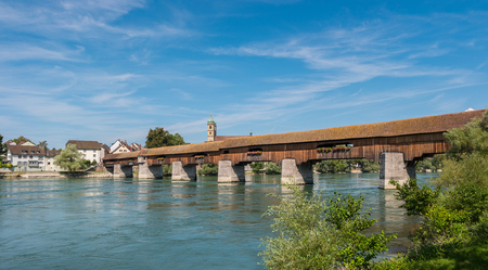 oldtown: The historic wood border bridge over Rhine river and Fridolins minster in Bad Saeckingen at summer, Black Forest, Baden-Wurttemberg, Germany, Europe Stock Photo