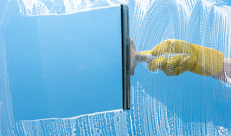 Hand in yellow rubber glove cleaning window on a blue sky Stockfoto