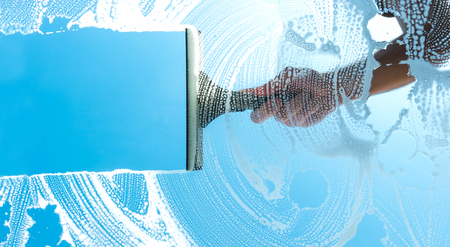 cleaning window squeegee with blue sky