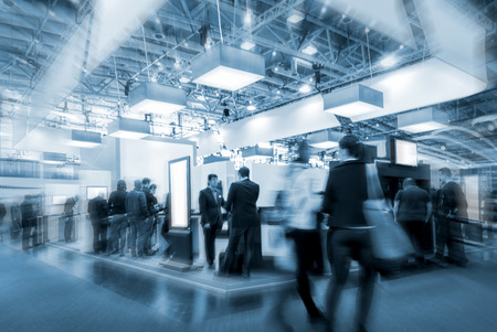 Blurred business people at a trade fair stand