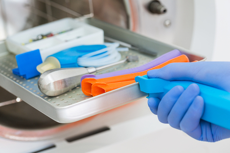 Young male dentist places medical autoclave for sterilising surgical and other instruments