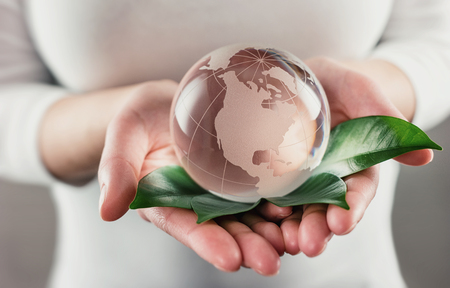 Protect the World - glass globe in hands Фото со стока