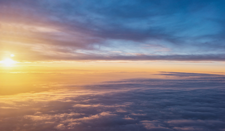 Sunset sky over the clouds background