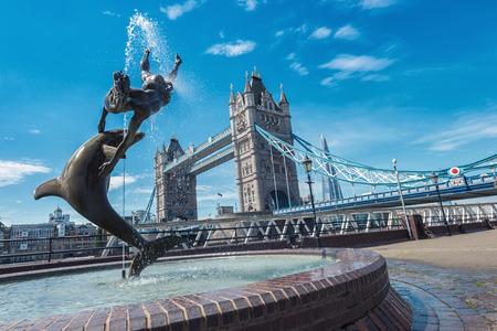 Tower Bridge en het standbeeld van een meisje die met dolfijn bij St Katharine dokken in Londen spelen.