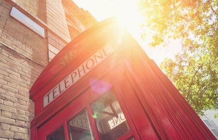 payphone: Red Telephone Booth with sun at summer in London street Stock Photo
