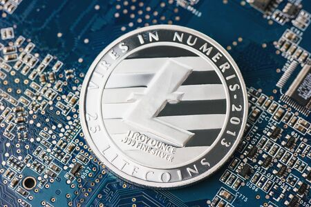 silver coins: Litecoin new digital cryptocurrency on mainboard Stock Photo
