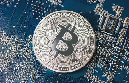 Bitcoin on a computer chip on motherboard Фото со стока