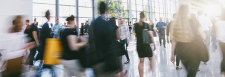 Crowd of anonymous people walking in a modern hall Stock Photo