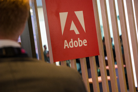 COLOGNE, GERMANY SEPTEMBER, 2017: Adobe Systems Logo with business man. Adobe is a multinational software company that produces and sells multimedia and creativity software.