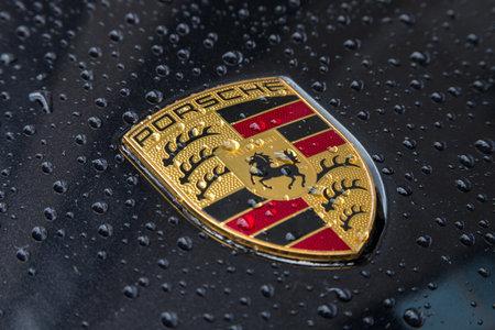 LONDEN, HET VERENIGD KONINKRIJK MEI 2017: Porsche Logo Close Up op een zwarte auto met regendruppels. Ferdinand Porsche richtte het bedrijf in 1931 op met hoofdkantoren in het centrum van Stuttgart.