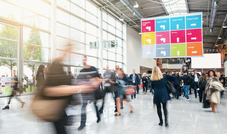 Anonymous blurred business people rushing in a hall of a trade fair