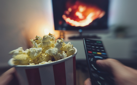 young man watching a movie with popcorn and remote controller, Point of view shot