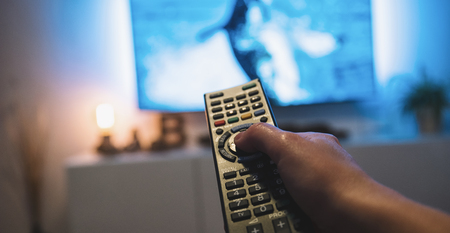 woman watching tv and using remote control, pov shot Stock Photo
